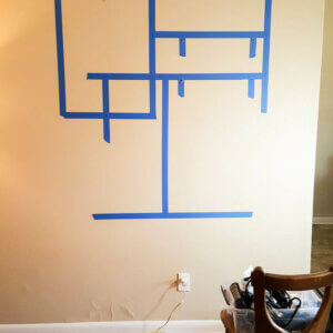 A wall marked out with blue tape before hanging
