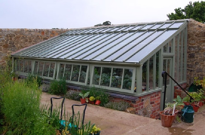 semi underground greenhouse surrounded on two sides with a stone wall and earth behind via solarinnovationscom - Earth Sheltered Greenhouse Plans